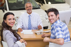 Portrait of smiling salesman and his clients. At new car showroom stock images