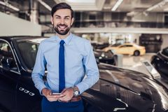 Smiling salesman in dealership salon. Portrait of smiling salesman standing at the car with smartphone in dealership salon royalty free stock images