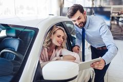 Salesman talking with client sitting in the car stock images