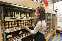 Portrait of smiling saleswoman arranding products in supermarket royalty free stock photo