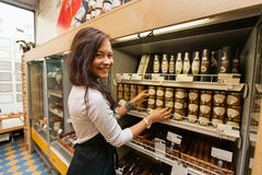 Portrait of smiling saleswoman arranding products in supermarket Stock Photography