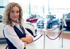 Portrait of smiling saleswoman standing in showroom. Portrait of smiling saleswoman with arms crossed standing in car showroom royalty free stock photography
