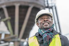 African American engineer, portrait outdoors. Portrait of a smiling and satisfied African American engineer wearing protective workwear looking upwards on stock images