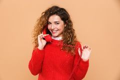 Portrait of a smiling satisfied girl talking. On a landline telephone  over beige background Stock Photos