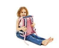 Portrait of smiling school girl hugging rucksack Stock Photography