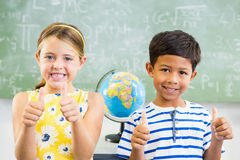 Portrait of smiling school kids showing thumbs up in classroom. At school Stock Photography