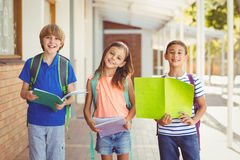 Portrait of smiling school kids standing in school corridor. With books Stock Images