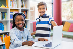 Portrait of smiling school kids using a laptop in library Royalty Free Stock Image