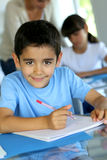Portrait of smiling school pupil with pen and notebook Royalty Free Stock Image
