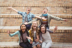 Portrait of smiling school students sitting on staircase having fun in campus Stock Photo