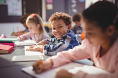 Portrait of smiling schoolboy doing his homework in classroom. At school Royalty Free Stock Photos