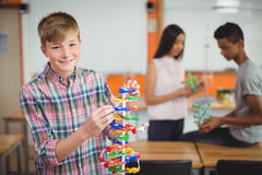 Portrait of smiling schoolboy examining the molecule model in laboratory Stock Photography