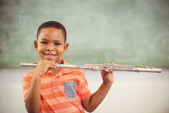 Portrait of smiling schoolboy playing flute in classroom Royalty Free Stock Image