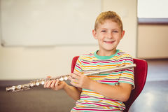 Portrait of smiling schoolboy playing flute in classroom Stock Photography