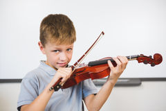 Portrait of smiling schoolboy playing violin in classroom Royalty Free Stock Images