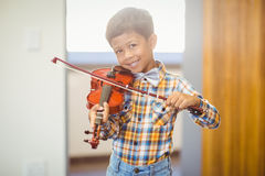 Portrait of smiling schoolboy playing violin in classroom Royalty Free Stock Image