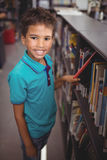 Portrait smiling schoolboy selecting book in library. At school Stock Photos