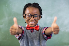 Portrait of smiling schoolboy showing thumbs up in classroom. At school Royalty Free Stock Photo