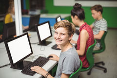 Portrait of smiling schoolboy studying in computer classroom Royalty Free Stock Photos