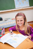 Portrait of a smiling schoolgirl drawing Stock Images