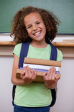 Portrait of a smiling schoolgirl holding her books. In a classroom Stock Image