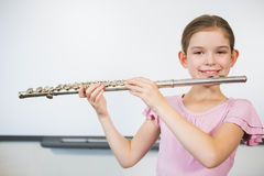 Portrait of smiling schoolgirl playing flute in classroom Stock Photos