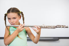 Portrait of smiling schoolgirl playing flute in classroom Stock Images