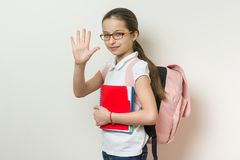 Portrait of a smiling schoolgirl 10 years old with glasses, with a backpack, notebooks giving high five to camera. Background bright wall in school royalty free stock image