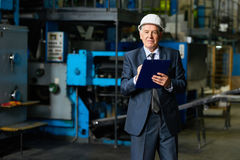 Factory Owner in Workshop. Portrait of smiling senior businessman wearing hardhat looking at camera holding clipboard in workshop of modern factory stock photo