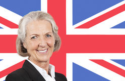 Portrait of smiling senior businesswoman over British flag Royalty Free Stock Photo