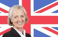 Portrait of smiling senior businesswoman over British flag royalty free stock photo