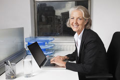 Portrait of smiling senior businesswoman using laptop at desk in office Stock Photos