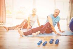 Portrait of smiling senior couple doing yoga Stock Images