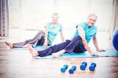Portrait of smiling senior couple doing yoga. Portrait of smiling senior couple performing yoga at home stock photo