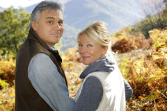 Portrait of smiling senior couple in forest in automn season Royalty Free Stock Images
