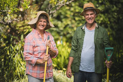 Portrait of smiling senior couple holding tools at yard Royalty Free Stock Images