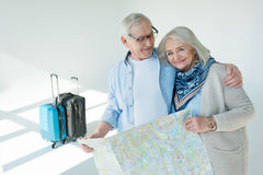 Portrait of smiling senior couple holding traveling map Stock Photos