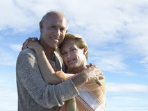 Portrait of smiling senior couple hugging each other against cloudy sky Stock Photography