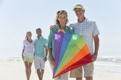 Portrait of smiling senior couple with kite on sunny beach stock image
