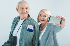 Portrait of smiling senior couple with passports and tickets making selfie on smartphone. Traveling concept Stock Photo
