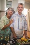 Portrait of smiling senior couple preparing food in kitchen Stock Images