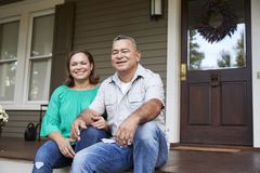 Portrait Of Smiling Senior Couple Sitting In Front Of Their Home stock images