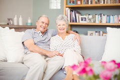 Portrait of smiling senior couple sitting on sofa in living room Royalty Free Stock Photography