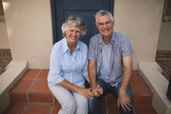 Portrait of smiling senior couple sitting together against house Royalty Free Stock Photo