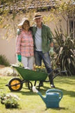 Portrait of smiling senior couple standing by wheel borrow in yard. Portrait of smiling senior couple standing by wheel borrow on field in yard royalty free stock images