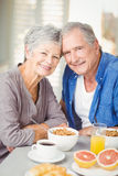 Portrait of smiling senior couple at table with breakfast Stock Photo