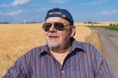 Portrait of smiling senior farmer standing at the wheat field edge and satisfied with future harvest Stock Images