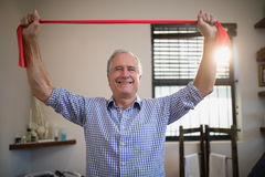 Portrait of smiling senior male patient holding red resistance band Royalty Free Stock Images