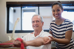 Portrait of smiling senior male patient pulling red resistance band with female doctor Royalty Free Stock Image