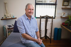 Portrait of smiling senior male patient sitting on bed against window Royalty Free Stock Images